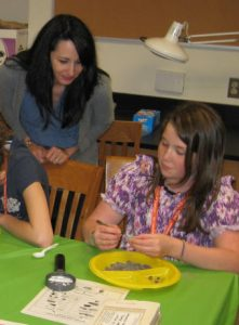 "IQPR graduate student Niki Garland looks over the shoulder as a girl scout explores the mastodon ""mud!"""